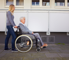 elder female in wheelchair and staff